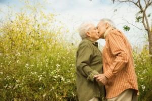 Elderly Couple Kissing in Meadow --- Image by © Hill Street Studios/Corbis